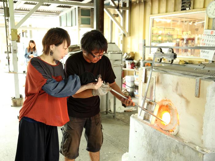「吹きガラス簡単コース」 1.1300℃にもなる窯の中で溶けたガラスをすくいとる。