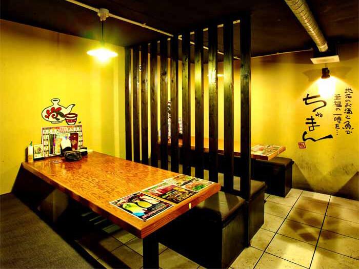 [恩納前兼久店] 地下1樓的桌位區,可坐4到6人。半開放式的禁菸包廂座