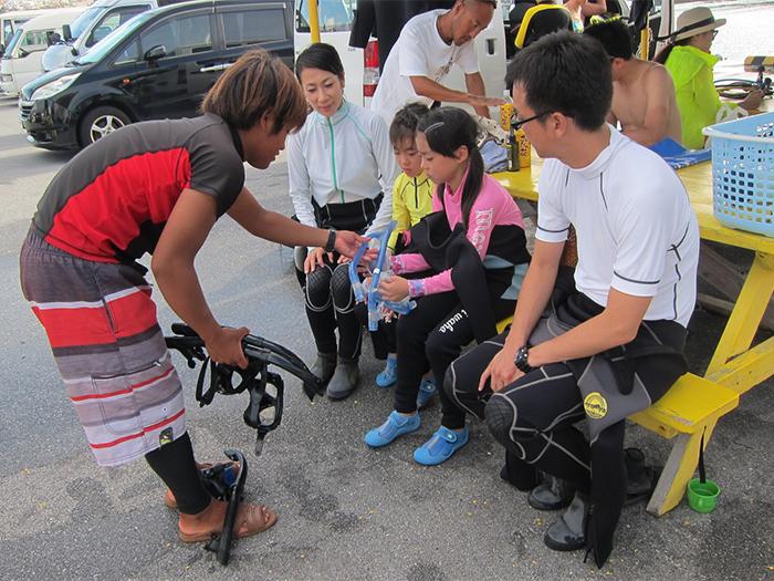 會說中文的日本人教練對第一次體驗潛水或浮潛的顧客做詳細的說明