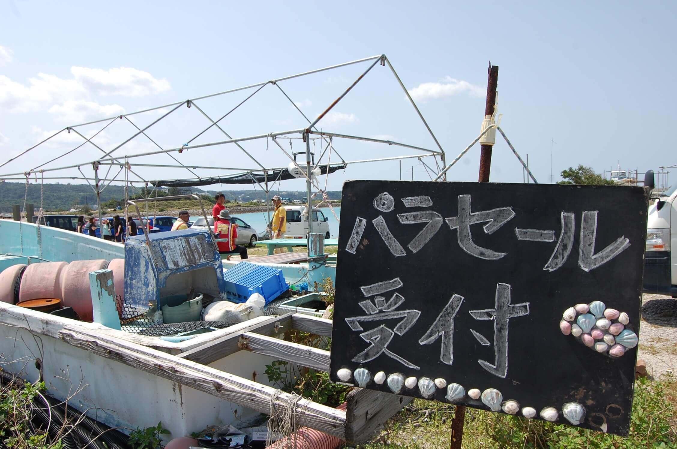 拖曳傘的報名處在漁港入口進去約80公尺前方的角落。